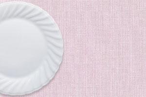 ピンクの布の上の白い丸皿